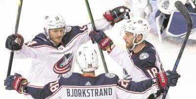 Columbus'Oliver Bjorkstrand is congratulated by teammates Gustav Nyquist, left, and Pierre-Luc Dubois after scoring against Tampa Bay during a Stanley Cup first round playoff game action in Toronto.