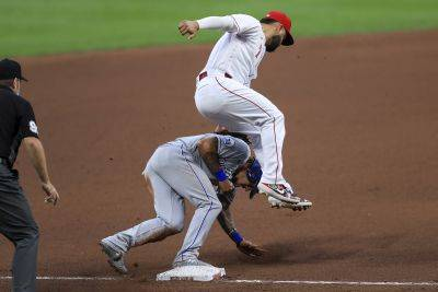 The Reds' Eugenio Suarez leaps over and applies the tag as Kansas City's Adalberto Mondesi steals third base safely on a wild pitch during Wednesday night's game in Cincinnati. (AP photo)