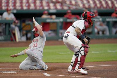 Cincinnati's Jesse Winker scores past Cardinals catcher Yadier Molina during Thursday night's game in St. Louis. (AP photo)