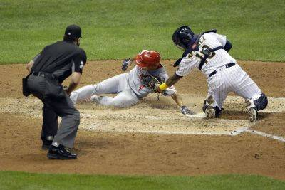 Cincinnati's Shogo Akiyama slides in safely at home past the tag attempt of the Brewers' Omar Narvaez during the second game of Thursday's  doubleheader in Milwaukee. (AP photo)