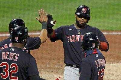 Cleveland's Carlos Santana, top right, is greeted as he returns to the dugout after hitting a three-run home run during the 10th inning of Tuesday night's game in Pittsburgh. The Indians won 6-3. (AP photo)