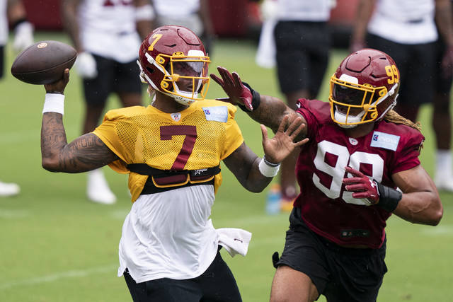 Washington quarterback Dwayne Haskins Jr. (7) passes under pressure from defensive end Chase Young (99) during an NFL football practice at FedEx Field, Monday in Washington.