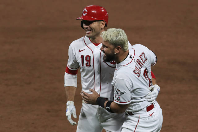 Cincinnati Reds' Joey Votto, left, is greeted by Eugenio Suarez, right, after hitting a walk-off RBI single in the ninth inning during a baseball game against the St. Louis Cardinals in Cincinnati, Wednesday, Sep. 2, 2020. (AP Photo/Aaron Doster)