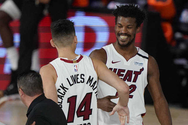 Miami Heat's Tyler Herro (14) and Jimmy Butler (22) react after the Heat beat the Milwaukee Bucks 116-114 in an NBA conference semifinal playoff basketball game Wednesday, Sept. 2, 2020, in Lake Buena Vista, Fla. (AP Photo/Mark J. Terrill)