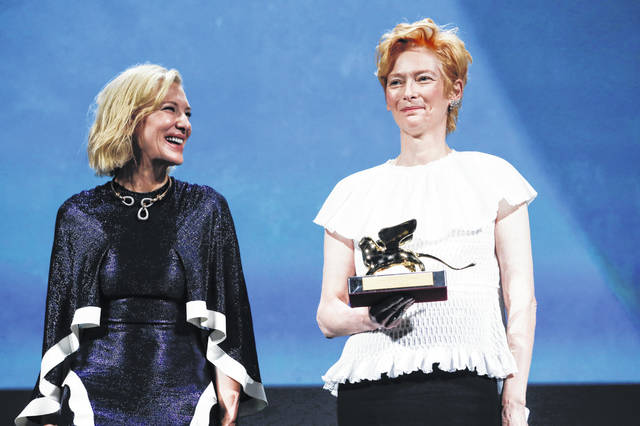 Actress Tilda Swinton, right, holds the Golden Lion for Lifetime Achievement, which was presented by Jury President Cate Blanchett during the opening ceremony of the 77th edition of the Venice Film Festival in Venice, Italy, on Wednesday.
