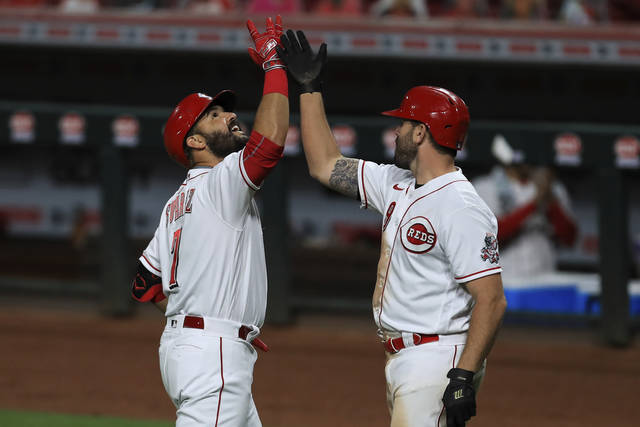 Cincinnati Reds' Eugenio Suarez, left, celebrates after hitting a two-run home run with teammate Mike Moustakas, right, in the sixth inning during a baseball game against the Milwaukee Brewers in Cincinnati, Monday, Sept. 21, 2020. (AP Photo/Aaron Doster)
