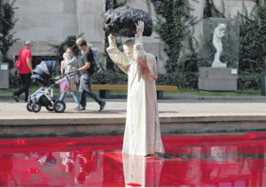 Sculpture of John Paul II with rock, red water makes waves