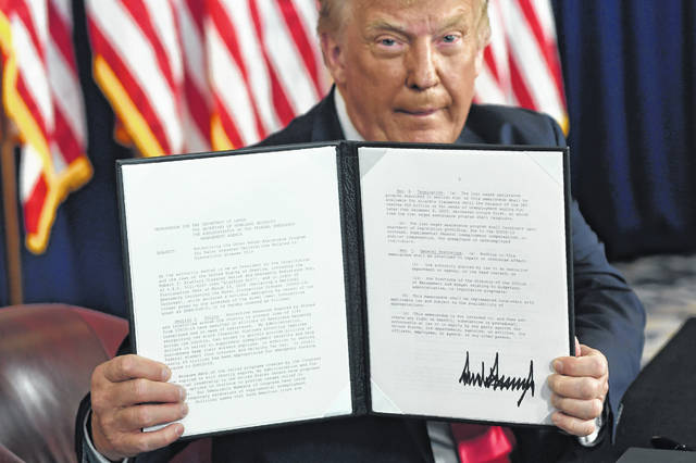 President Donald Trump holds up an executive order he signed to addresses the economic fallout from the COVID-19 pandemic. Trump allowed people to defer payroll taxes, with the rule going into effect last week.