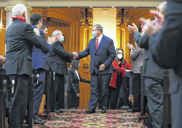 Bob Cupp, R-Lima, center, is congratulated after being elected Speaker of the House at the Ohio Statehouse in Columbus, Ohio on Thursday, July 30, 2020. Cupp created the newly formed House Select Committee on Energy Policy and Oversight, which will convene to work on efforts to repeal and replace a controversial bailout law that brought down the former Ohio House speaker in the aftermath of a $60 million federal bribery probe.