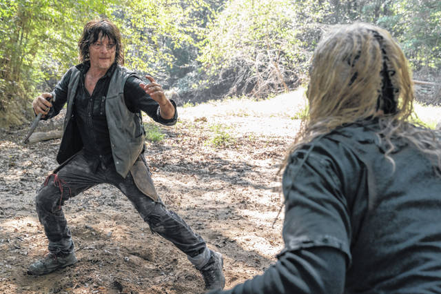 """This image released by AMC shows Norman Reedus, left, and Samantha Morton in a scene from """"The Walking Dead."""" The AMC channel says its series will wrap with an 11th season spanning 24 episodes and two years. When """"The Walking Dead"""" is laid to rest in late 2022."""