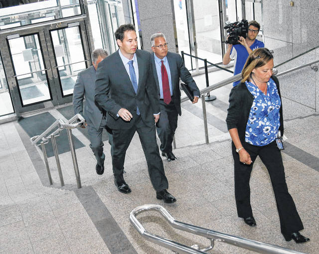 FILE—In this file photo from June 5, 2019, former Dr. William Husel, center, arrives at the downtown Columbus Division of Police headquarters in Columbus, Ohio. An Ohio hospital system has reached more settlements related to Husel, who is accused of ordering excessive painkillers for dozens of patients and has pleaded not guilty to 25 counts of murder. The related settlements involving the Columbus-area Mount Carmel Health System now total more than $16.7 million. That includes three settlements of $750,000 each that were filed in the past two weeks.