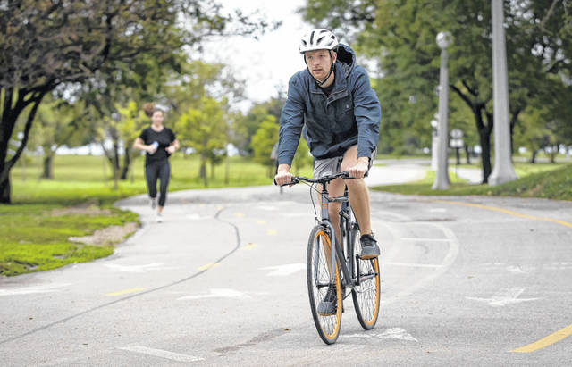 Ben Meeder rides his new bike Wednesday on the Lakefront Trail in Chicago. His employer, software company ServiceNow, paid for the bike.