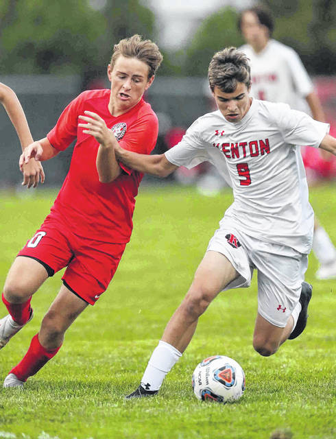 Kenton's Tristan Speirs (9) tries to hold off Bluffton's Jude Spallinger during Thursday night's match in Bluffton.