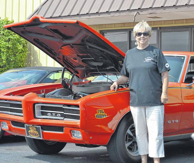 Vicky Allen poses with a 1969 Pontiac GTO that she and her late husband Gary owned. Close to 200 cars were on display at the Gary Allen Memorial Car Cruz-In Sunday at Tom's Auto Detail.