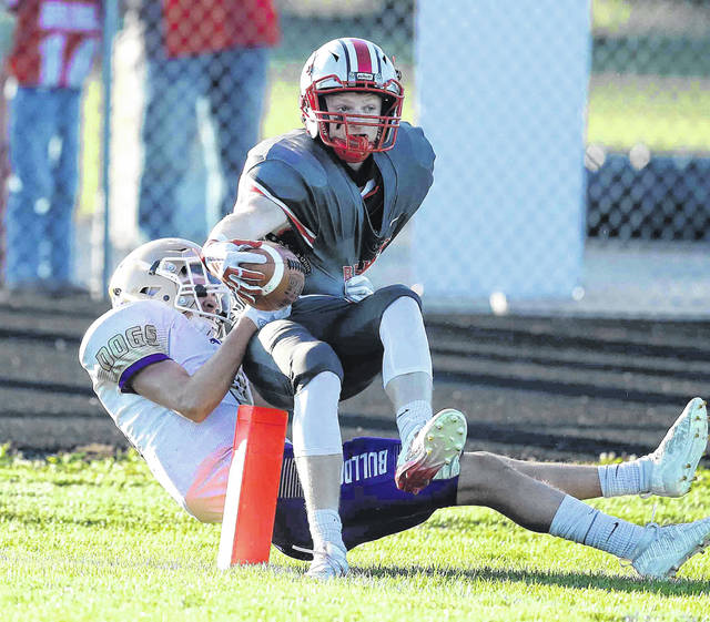 Columbus Grove's Colin Metzger is able to get a touchdown before Ada's Trent Ennis can bring him down during Friday night's game at Columbus Grove.