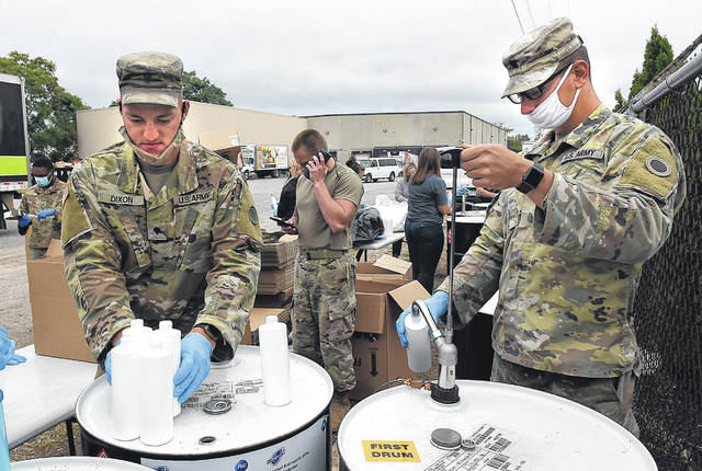 SPC Justin Dixon, left, and SPC Cole Gagnon, of the Ohio National Guard, fill bottles of hand sanitizer with other area volunteers at West Ohio Food Bank on Friday as part of the United Way of Greater Lima's fifth annual Annual Day of Caring.