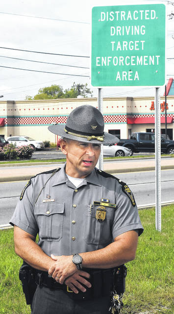 Lt. Tim Grigsby addresses media during a distracted driving target enforcement area event along state Route 309 on Monday.