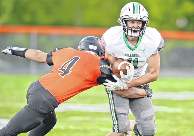 Celina's Conner Altstaetter tries to get away from Elida's Tyler Carter during Friday night's game at Elida. See more game photos at LimaScores.com.