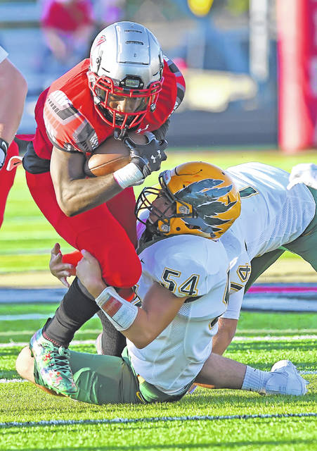 Lima Senior's Cam Miles fights for yardage against Oregon Clay's Nate Howard during Friday night's game at Spartan Stadium.
