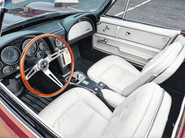 The interior of the 1965 Chevy Corvette Roadster includes a teak steering wheel.