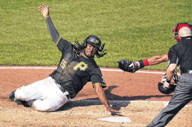 Josh Bell, of the Pittsburgh Pirates, slides past the tag attempt by Cincinnati Reds catcher Curt Casali for the tying run in the bottom of the ninth inning of the Pirates' 3-2 win over the Reds on Sunday in Pittsburgh. The Pirates scored two runs in the ninth inning for the win.