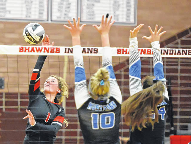 Shawnee's Gracie Freiberger hits a spike against Allen East's Kristin Whitley (10) and Hannah Williams during Tuesday night's match at Shawnee.