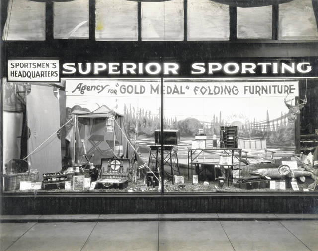 Superior Sporting Goods' display window is decorated in an outdoor theme, from camping furniture to picnic baskets to fishing rods. This photograph is undated.