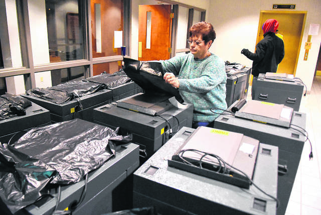Kathy Meyer, director of the Allen County Board of Elections, covers ballot machines with plastic bags before sending them off to polling locations throughout the county in November 2018.