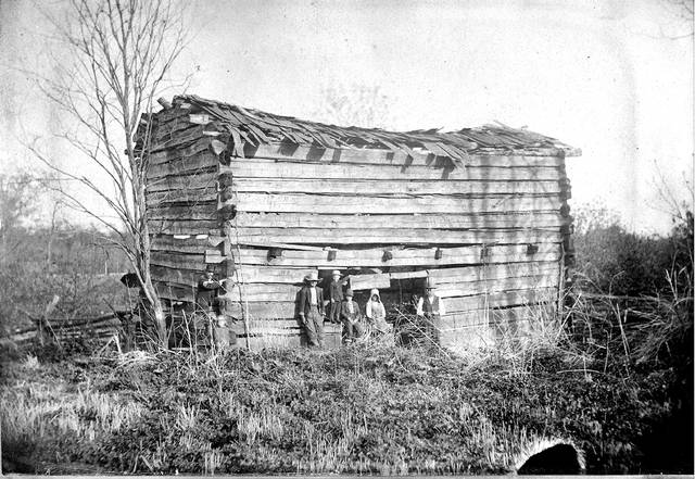 This photo, from about 1878 or '79, shows the Hover family with the former councilhouse built under the direction of PHT. It was built in 1831, had two stories, featured a fireplace and was overall said to be of fine workmanship. It was used for public occasions by the Shawnee. After they were removed from this area, the structure was a temporary dwelling from the Griffith, Breese and Ezekiel Hover families. In the photo are Ezekiel Hover, Joe Hover, Howard and Anna Hover and David E. Hover along with two unidentified people.