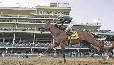 Jockey John Velazquez riding Authentic, right, crosses the finish line Saturday ahead of Tiz the Law to win the 146th running of the Kentucky Derby at Churchill Downs in Louisville, Ky.