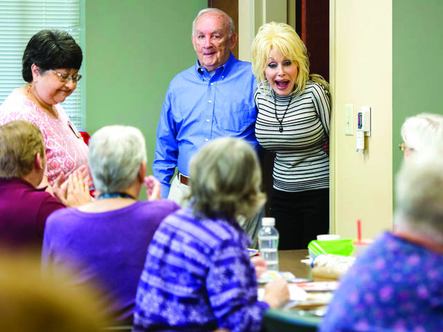 Country music superstar Dolly Parton, back right, surprises a quilting class at the renamed My People Senior Activity Center in Sevierville, Tenn., in May 2018. (Brianna Paciorka/Knoxville News Sentinel via AP)