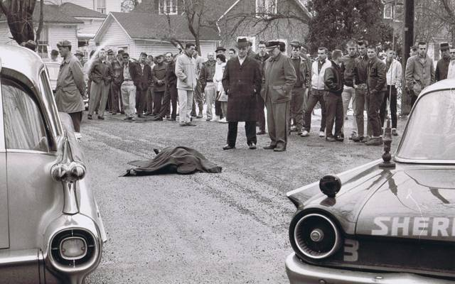 """A crowd gathers at a 1962 crime scene. Elida's mayor and constable Clarence """"Pops"""" Prince was shot and killed in front of Elida school."""