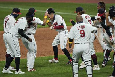 The Indians' Cesar Hernandez, center, is mobbed by teammates after hitting an RBI-single in the ninth inning during Saturday night's game against Milwaukee in Cleveland. (AP photo)