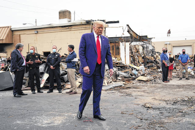 President Donald Trump tours an area damaged during demonstrations.
