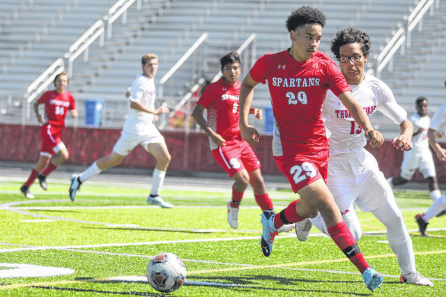 Lima Senior's Curtis Williams (29) tries to keep Lima Central Catholic's Frankie McDonald from getting to the ball during Saturday's match at Spartan Stadium.
