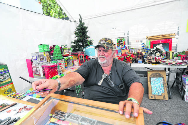 David Siders, of Lima, shows a spring assisted pocket knife at Max's Trader Days and Water Dog Races at the Allen County Fairgrounds.