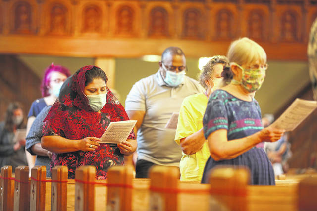 Visitors sing during a prayer service hosted by St. John and St. Rose held at St. Rose on Tuesday evening.