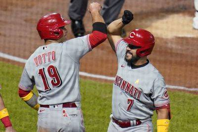 The Reds' Eugenio Suarez (7) celebrates with Joey Votto (19) as he returns to the dugout after hitting a three-run home run off during Saturday night's game against the Pirates in Pittsburgh. (AP photo)