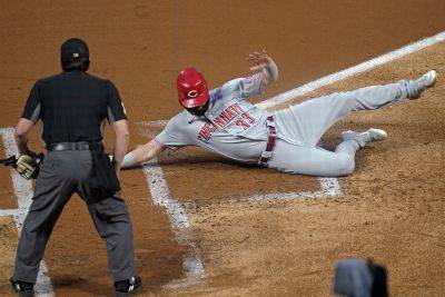 Cincinnati's Jesse Winker scores on a sacrifice fly by Mike Moustakis during Saturday night's game against the Minnesota Twins in Minneapolis. (AP photo)
