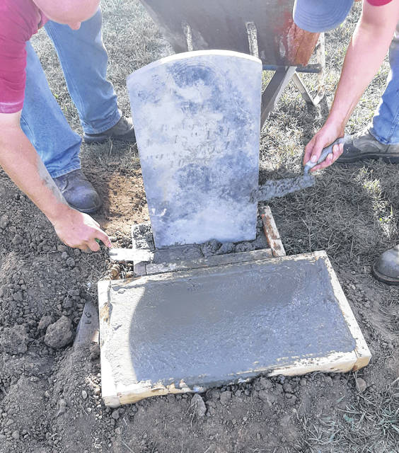 Volunteers work to reset the original marker of William Rodgers and install a new stone.