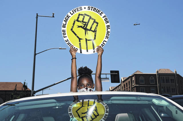 Audrey Reed, 8, holds up a sign through the sunroof of a car during a rally in Los Angeles.