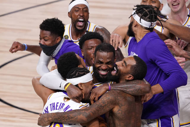 Los Angeles Lakers' LeBron James (23) celebrates with his teammates after the Lakers defeated the Miami Heat 106-93 in Game 6 of basketball's NBA Finals Sunday, Oct. 11, 2020, in Lake Buena Vista, Fla. (AP Photo/Mark J. Terrill)