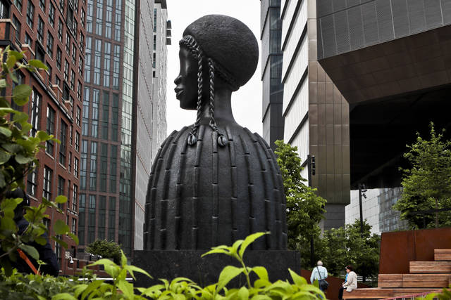 """In this May 29, 2019 , file photo, a bronze bust of a Black woman entitled """"Brick House,"""" by Chicago artist Simone Leigh, stands among buildings and vegetation in the High Line park in New York. Leigh will be the first Black woman ever to represent the U.S. at Italy's prestigious Venice Biennale arts festival to be held in 2022. (AP Photo/Bebeto Matthews, File)"""