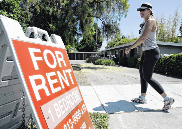 """A woman walks next to a """"For Rent"""" sign at an apartment complex in Palo Alto, Calif. Many tenants aren't familiar with the ins and outs of their renters insurance policies, but what they don't know could cost them money."""