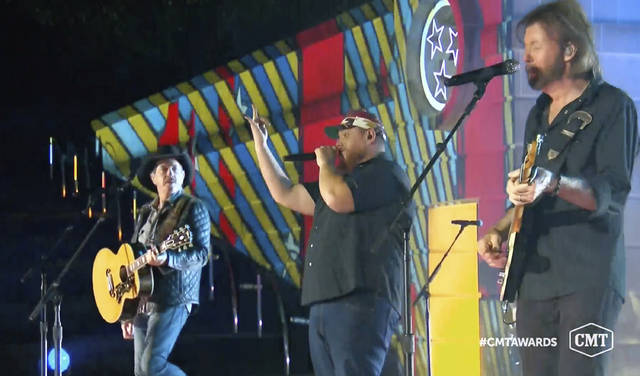 """In this video image provided by CMT, Kix Brooks, from left, Luke Combs and Ronnie Dunn perform """"1, 2 Many"""" during the Country Music Television awards airing on Wednesday."""