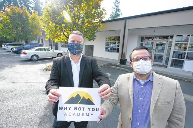 Garth Reeves, left, and Scott Canfield, co-founders of the Why Not You Academy charter school, pose for a photo with the school's new name and logo Tuesday in front of the building that will house the school in Des Moines, Wash., south of Seattle. Seattle Seahawks NFL football quarterback Russell Wilson and his Grammy-winning wife, pop singer Ciara, are putting their money and celebrity behind rebranding the charter school, which advocates hope will boost the troubled Washington state charter school sector that has suffered from enrollment problems after years of legal challenges.