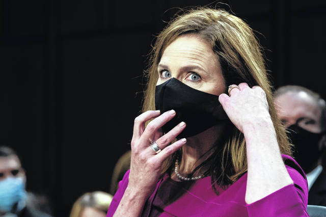 Supreme Court nominee Amy Coney Barrett adjusts her face mask after speaking during her Senate Judiciary Committee confirmation hearing on Capitol Hill in Washington on Monday.