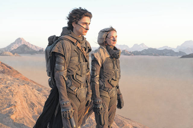 """This image released by Warner Bros. Entertainment shows Timothee Chalamet, left, and Rebecca Ferguson in a scene from """"Dune."""" Warner Bros. said late Monday that its sci-fi pic """"Dune"""" will now open in October 2021, instead of this December. The studio also pushed back it's """"Matrix"""" sequel by 8 months to late 2021 and """"The Batman"""" to 2022."""