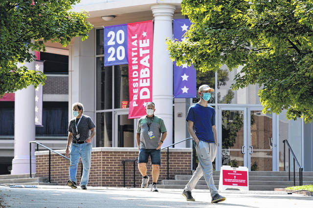 People walk outside the Curb Event Center at Belmont University as preparations take place for the second Presidential debate, Tuesday, Oct. 20, 2020, in Nashville, Tenn. President Donald Trump and Democratic presidential candidate, former Vice President Joe Biden are scheduled to debate Thursday, Oct. 22.