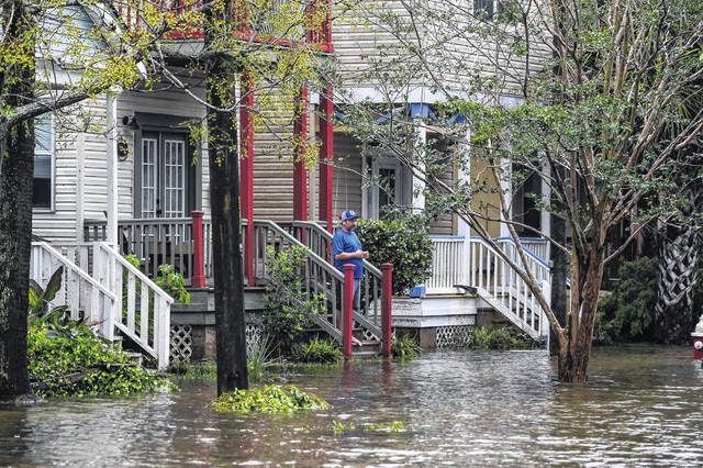 A man stands outside his home, watching a street flooded by Hurricane Sally in Pensacola, Florida, on Sept. 16.